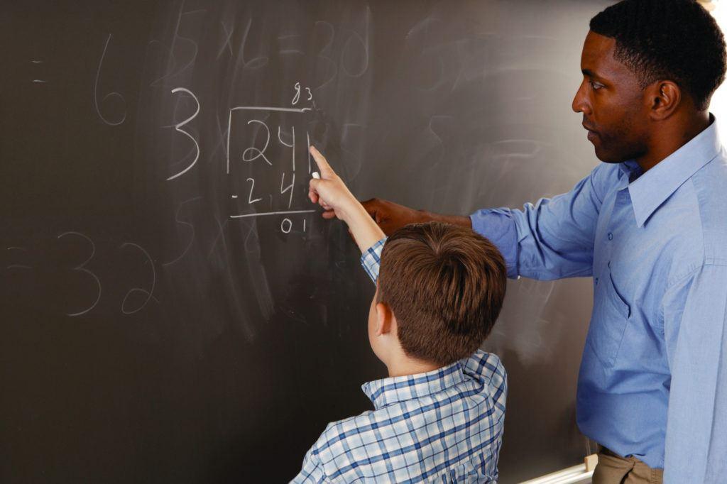 Teacher helping student with math problem transtorno da matemática - 78494416 1024x682 - Transtorno da matemática. O seu filho tem?